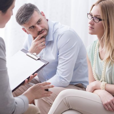 Upset young woman talking to a female psychologist with her husband aside